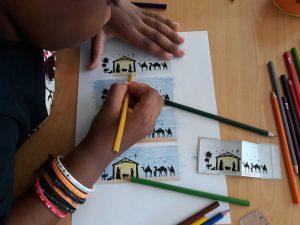 Um aluno pinta os presépio em folhas de papel.