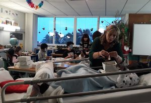A sala com vários alunos, sentados à volta de uma mesa e numa cama, fazem trabalhos com a ajuda das mediadoras culturais.