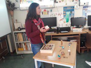 A Ana mostra objetos pequenos que retira de uma caixa.