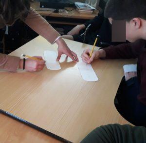 Um aluno escreve num marcador de livro o seu nome com hieróglifos.