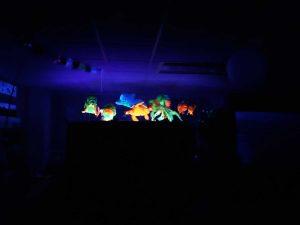 Num fundo escuro, veem-se bonecos coloridos e brilhantes que representam as personagens da peça de teatro: tartaruga, peixes, golfinhos e um polvo.