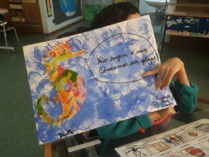 Um aluno segura o seu anúncio onde se observa um cavalo-marinho colorido num fundo azul e um balão de fala que diz: Não sujem o mar! Queremos ser felizes!