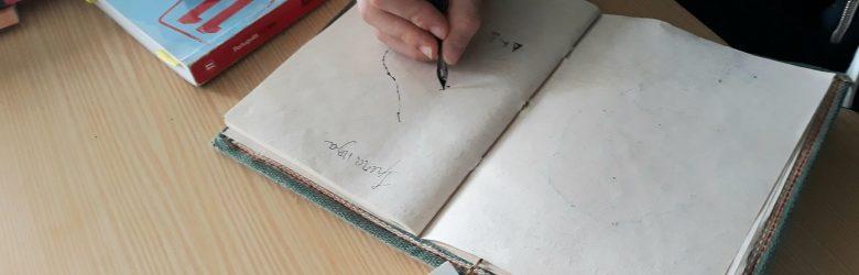 Um aluno escreve com caneta de pena e aparo num caderno de folhas recicladas.