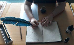 Um aluno experimenta a caneta de pena e aparo para desenhar e escrever.