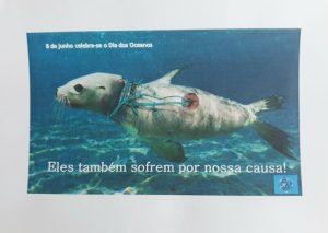 Anúncio elaborado no Paint onde se vê uma foca enrolada em redes de pesca. O slogan diz: Eles também sofrem por nossa causa!