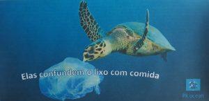 Anúncio elaborado no Paint onde se v|e a fotografia de uma tartaruga a comer um saco plástico. O slogan diz: Eles confundem o lixo com comida!