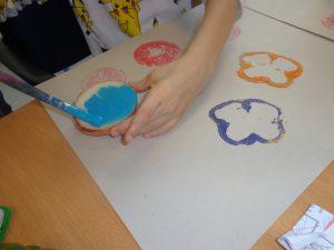 Mão a pintar legume para servir de carimbo