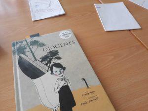 """O livro """"Diógenes"""" encontra-se fechado em cima de uma secretária. Nele observamos um jovem com um saco às costas e com uma árvore e um barco dentro."""