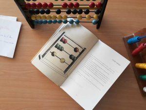 O livro aberto em cima de uma secretária com a ilustração de um ábaco. Ao lado do livro vemos dois ábacos diferentes.