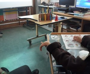 A mão de um aluno aponta para os ábacos que se encontram sobre uma secretária.