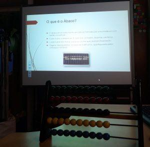 No quadro interativo, observamos um diapositivo com informações acerca do ábaco. Em primeiro plano, um ábaco em cima de uma secretária.