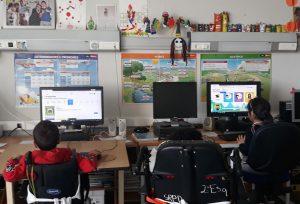 Um grupo de três alunos encontra-se em frente a computadores a seguir uma aula da plataforma ubbu.