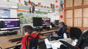 Um grupo de alunos encontra-se em frente de computadores a visionar um dos vídeos da plataforma ubbu.