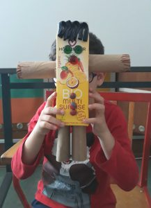 Um aluno mostra o seu robô concluído feito com uma embalagem de sumo, dois rolos de papel higiénico, tampas e fita.
