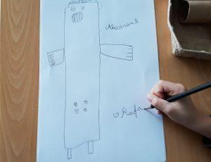 A mão de um aluno a desenhar o seu projeto robô.