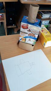 Um robô começa a tomar forma com materiais reciclados: caixa de bolachas e um rolo de papel higiénico.