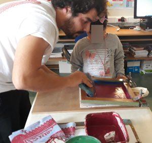 O Gonçalo Marau ensina a uma aluna como segurar na raclete para que a tinta fique bem distribuída.