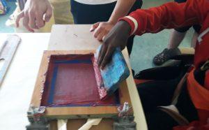 Um aluno utiliza a raclete para fazer a impressão nos sacos.