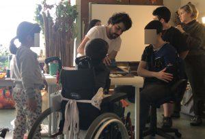 Vários alunos à volta da mesa onde se encontram os materiais de serigrafia e o Gonçalo a ensinar-lhes o processo de impressão.