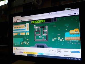 o monitor de um computador mostra o trabalho de um aluno: criar algoritmos para que um carro virtual siga o seu caminho até ao destino.
