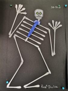 Esqueleto de cotonetes sobre cartolina preta com gravata azul