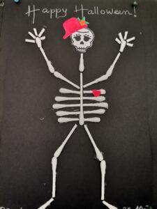 Esqueleto de cotonetes sobre cartolina preta com chapéu e coração coloridos