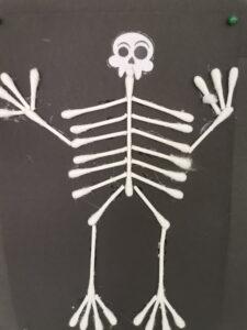 Esqueleto de cotonetes sobre cartolina preta