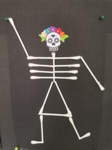 Esqueleto de cotonetes sobre cartolina preta com flores na cabeça