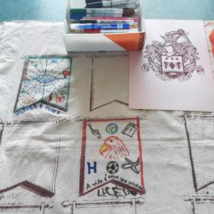 Pano estendido sobre uma secretária com dois brasões feitos. Em cima, encontra-se o brasão da família O'Neil em serigrafia.