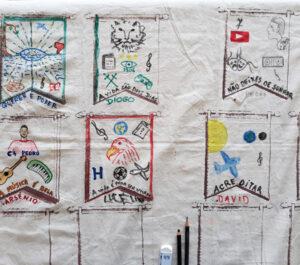 Um pano com várias divisórias e em cada uma vários desenhos indicadores dos gostos dos alunos: um leão, viola, representação de um eclipse lunar, rostos, símbolo do youtube, etc..