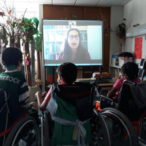 Alunos de costas a comunicarem por videoconferência com a Ana cuja imagem se encontra projetada num quadro interativo.