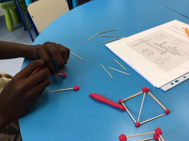 Mãos de aluno a construir sólidos geométricos com ajuda de palitos e plasticina