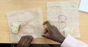 Dois pedaços de pão são colocados pela aluna dentro de dois sacos de plástico identificados como A e B.