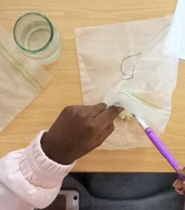 A aluna pincela o pão do saco B com gotas de água.