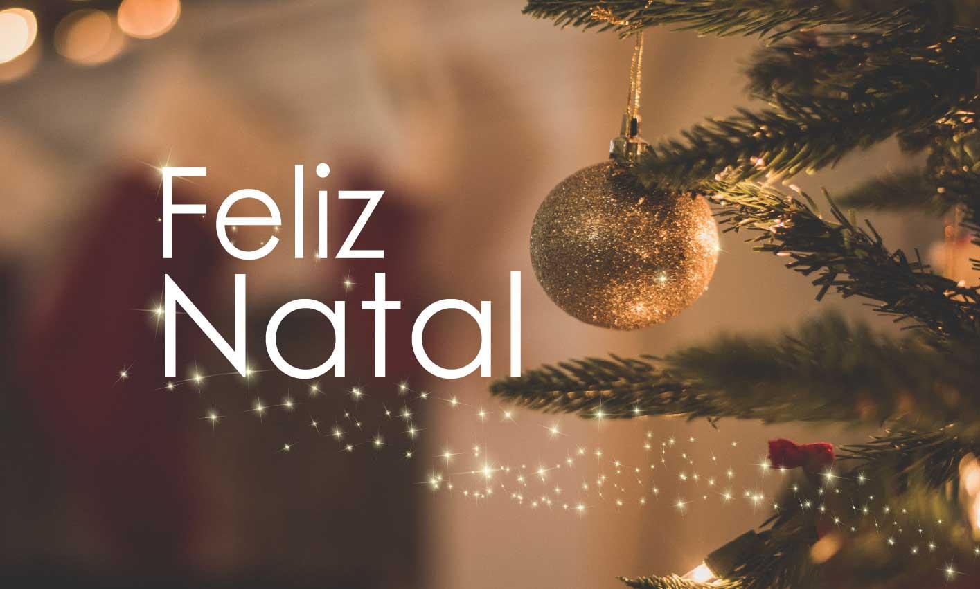 Texto Feliz Natal sobre foto de árvore de Natal e bola