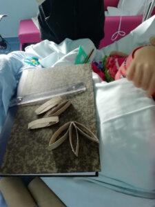 Criança na cama constrói uma estrela de Natal