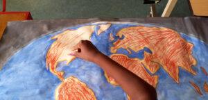 Uma aluna pinta o globo terrestre.