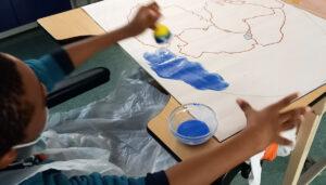 Um aluno pinta o mar à volta de um mapa com a representação da Pangeia.