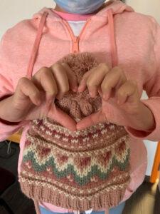 Criança com um gorro fazendo o gesto de um coração com as mãos