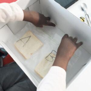 A aluna coloca os dois sacos com pão dentro de uma caixa .