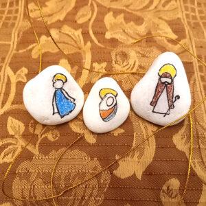 Um presépio com três pedras: uma com a figura de Nossa Senhora, outra com a de São José e outra com a do Menino Jesus.