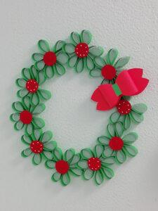 Coroa com flores de papel verdes e vermelhas