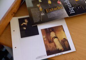 Em cima da mesa representações de quadros antigos e de revistas para fazer os recortes.