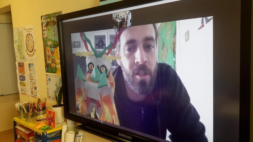 No ecrã, Pedro, do Museu da Marioneta, mostra a marioneta de um dragão