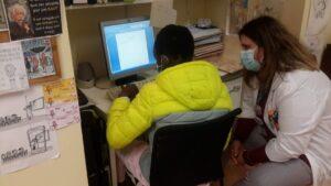 Aluno e professora junto ao computador a trabalhar