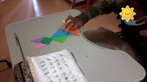 Aluno à mesa com peças de tangram