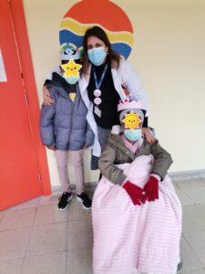 Professora e dois alunos à porta da escola