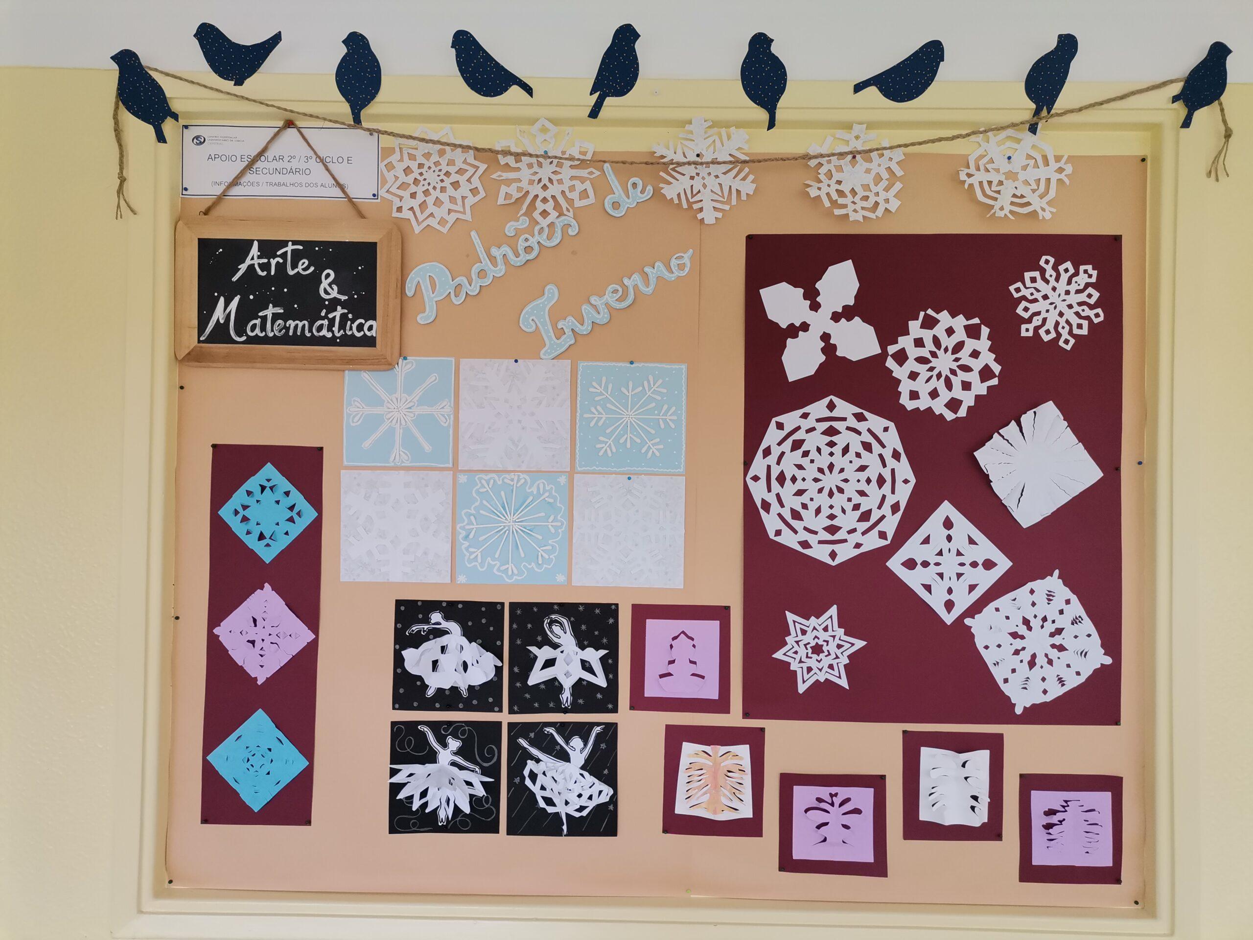 Flocos de neve e outras formas, algumas simétricas, recortadas em papel no placard da escola