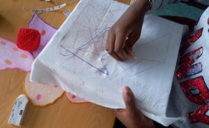 Uma aluna a bordar o seu desenho.