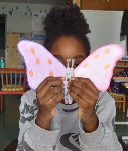 A aluna apresenta o seu trabalho final: a borboleta articulada.